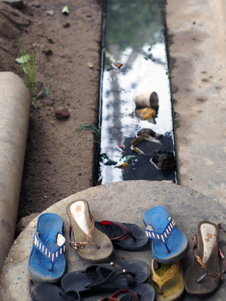 Shoes over the  open sewers outside a poor school